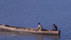 Den långa hemlagade träkanoten paddlade, Conakry port arkivfilmer