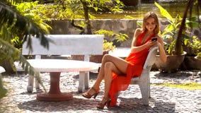 Den långa lade benen på ryggen flickan surfar internet på telefonen parkerar in arkivfilmer