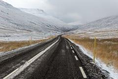 Den långa och blåsiga vägen i en dal sourrounded av snö täckte berg arkivbild