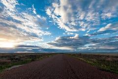 Den långa raka vägen försvinner in i den avlägsna horisonten under en solnedgånghimmel som är full av moln i vildmarken royaltyfri bild