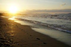 Den långa sandiga stranden med att skumma avfärdar och solnedgångsolen royaltyfri bild