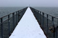 Den långa träpir som täckas i snö, når ut över vidsträckt vidd av krabbt vatten royaltyfri fotografi