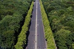 Den långa vägen med folk och inga bilar i gräsplan parkerar Arkivbilder