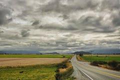 Den långa vägen sneddar över dalen, under att hägra moln royaltyfria foton