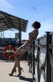 Den långbenta flickan i en kort klänning är på pir i himlen som flyger bir royaltyfria bilder
