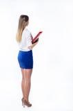 Den långhåriga flickan i kontoret beklär stående tillbaka Royaltyfri Bild