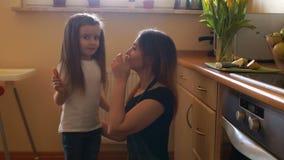 Den långhåriga flickan körde till hennes moder i köket En kvinna kramar hennes dotter och kysser henne lycklig hemmafru stock video