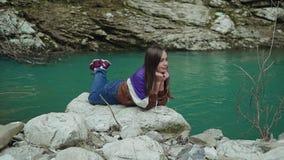 Den långhåriga flickan ligger på en stor sten nära en turkosbergsjö och dinglar hennes ben arkivfilmer