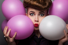 Den löjliga flickan med färgrikt luftar ballonger som tycker om Arkivbild