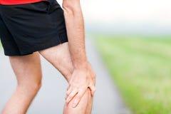 Den löparebenkalven och muskeln smärtar under rinnande sportutbildning utomhus arkivfoton