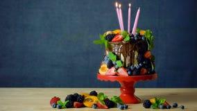Den l?ckra chokladdroppandekakan dekorerade med nya s?songsbetonade frukt och b?r stock video