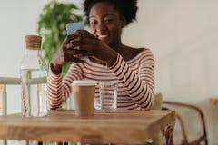 Den l?ga vinkeln av lyckliga afrikanska kvinnan som den har, vilar i kaf? royaltyfria foton