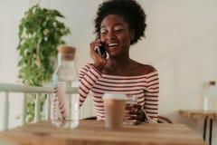 Den l?ga vinkeln av lyckliga afrikanska kvinnan som den har, vilar i kaf? royaltyfri foto