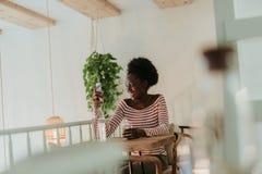 Den l?ga vinkeln av lyckliga afrikanska kvinnan som den har, vilar i kaf? royaltyfri bild