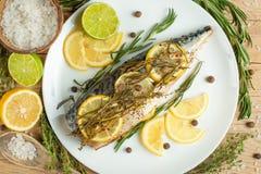 Den lagade mat makrillen på en vit platta med kryddor, örter, citron, kalkar och saltar En närbild, på en träbakgrund Begrepp av  arkivfoto