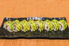 Den lagade mat sushi på en svart platta Arkivbilder