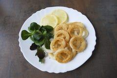 Den lagade mat tioarmade bläckfisken ringer med grön sallad och citronen Royaltyfri Bild