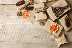 Den lantliga gåvan som slås in i hantverkpapper med naturlig garnering på trätabellen med, sörjer kottar Den enkla ecoen framlägg royaltyfri foto
