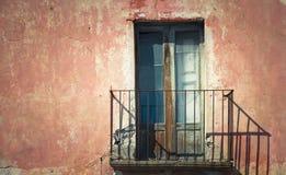 Den lantliga gamla grungy och red ut trästängda dörren av den rostiga balkongen med en röd brun tappning knäckte väggen royaltyfri foto
