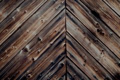 Den lantliga mörka antikviteten befläckte träväggen med åldrades spruckna träplankor och spikar i bygden - Grungy tappning royaltyfri foto