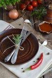 Den lantliga tabellinställningen med leraplattan, bestick, peppar maler, flaskor av vin, gräsplaner, grönsaker och kryddor Landss Royaltyfri Foto