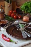 Den lantliga tabellinställningen med leraplattan, bestick, peppar maler, flaskor av vin, gräsplaner, grönsaker och kryddor Landss Fotografering för Bildbyråer
