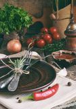 Den lantliga tabellinställningen med leraplattan, bestick, peppar maler, flaskor av vin, gräsplaner, grönsaker och kryddor Landss Arkivfoto