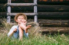 Den lata pojken ligger i gräs under ladugården - oförsiktig sommar på räkning royaltyfri fotografi