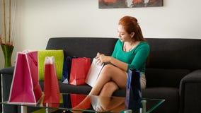 Den Latina flickan kikar in i shoppingpåsar på Sofa At Home Royaltyfri Foto