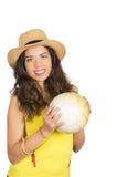Den latinamerikanska brunetten som bär den gula den fotbollskjortan och hatten som poserar för kamera, medan hållande, klumpa iho Arkivfoton