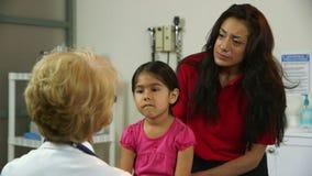 Den latinamerikanska mamman lyssnar fast beslutsamt till vilken doktor säger om sjukt barn arkivfilmer