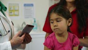 Den latinamerikanska mamman med dottern lyssnar till pediatriskt lager videofilmer