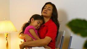 Den latinamerikanska mamman väntar i väntande rum för kliniken för att doktor ska se sjukt arkivfilmer
