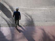 Den latinamerikanska mannen går på en gata och att se till sidan, flyg- sikt Royaltyfri Bild