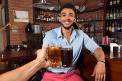 Den latinamerikanska mannen i stångfinkaexponeringsglas som rostar som dricker ölhållen, rånar, gladlynt vänmöte Royaltyfri Bild