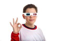 Den latinamerikanska pojken bär exponeringsglas 3D och gör det reko tecknet Arkivbilder
