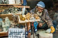 Den äldre mannen säljer hans konstprodukter Royaltyfria Bilder