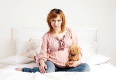 Den le härliga gravid kvinna sitter på en säng Arkivfoton