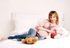 Den le härliga gravid kvinna sitter på en säng Royaltyfria Bilder