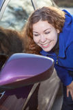 Kvinnan beundrar sig oneself i bil baksida-beskådar sidan avspeglar Fotografering för Bildbyråer