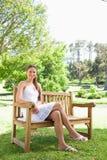 Den le kvinnan med henne ben korsade att sitta Royaltyfria Bilder