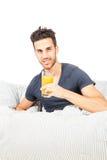 Den le mannen dricker orange fruktsaft i underlaget royaltyfri foto
