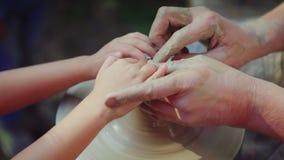 Den ledar- keramikern undervisar barnet hans expertis Begreppet är överföringen av erfarenhet vid utvecklingar arkivbild