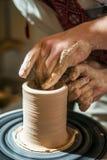 Den ledar- keramikern undervisar barnet hur man gör en tillbringare ut ur lera Arkivfoton