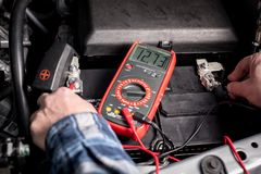 Den ledar- mekanikern testar spänningen av ett lastbilbatteri genom att använda en spänningsmeter royaltyfri fotografi