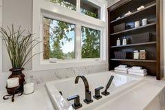 Den ledar- moderna badruminre i lyxhemmet med mörka ädelträkabinetter, vit badar och den glass dörrduschen royaltyfri bild