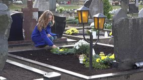 Den ledsna änkakvinnan satte stearinljuset på grav av maken i kyrkogård 4K arkivfilmer