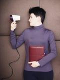 Den ledsna affärskvinnan ligger med den handheld personliga organisatören och hårtork på soffan Arkivfoton