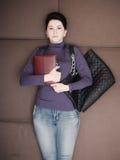 Den ledsna affärskvinnan ligger med den handheld personliga organisatören och handväskan på soffan Arkivbild