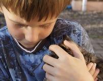 Den ledsna bekymrade pojken kramar kattungen Royaltyfri Bild